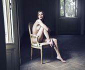 Beautiful naked woman sitting on an old chair in an empty room