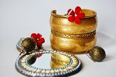 picture of dowry  - Indian bracelet with a picture of the sun, round mirror and earrings ** Note: Shallow depth of field - JPG