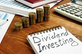 Dividend Investing Sign And Stacks Of Money. poster