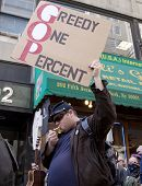 NEW YORK - MAY 1: A protester holds a sign that reads 'Greedy One Percent' during the march to Union