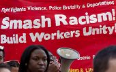 NEW YORK - MAY 1: Protesters march in front of a sign that in part reads 'Smash Racism ' during at U