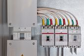 A Large Input Circuit Breaker And A Series Of Circuit Breakers With Cables Connected To Them. Each P poster