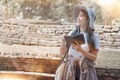 Beautiful Young Asian Female Traveler Writing On Notebook While Sightseeing In Popular Tourist Attra poster