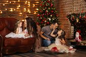 Family On Christmas Eve At Fireplace. Gift Boxes. Decorated Living Room With Traditional Fire Place. poster