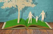 Paper cut of family symbol under tree on old grass book