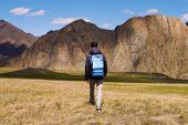 Tourist In A Cap And Jacket With A Backpack Goes On The Grass In The Direction Of Mountains. Explori poster