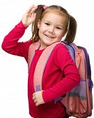 Portrait of a cute little schoolgirl with backpack, going to school and waiving bye-bye, isolated ov