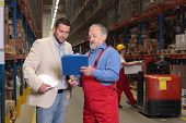 Manager And Supervosr Reading Papers In Warehouse