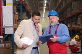 Supervisor And Senior Worker At The Meeting In Warehouse