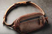 Handmade Genuine Brown Leather On A Dark Background Brown Belt Bag. Elegant Brown Bag With A Zipper poster