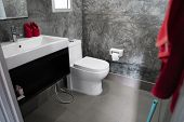 White Toilet In The Home Bathroom With A Sink And Red Towels On A Wall With Grey Tiles In Concrete S poster