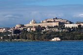 View from sea of Milazzo town in Sicily Italy with medieval castle on hilltop