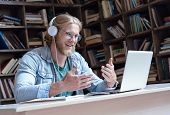 Happy Male Student Online Teacher Wear Headphone Talk Video Calling Looking At Laptop Computer Scree poster