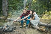 Couple In Love Enjoying Bonfire In Nature. Funny Couple Hikers Watching Fire Together On Camp. Happy poster