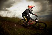 foto of dirt-bike  - Young man riding a mountain bike downhill style - JPG