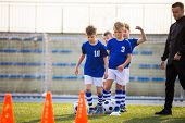 Boys Training Football On Pitch Witch Youth Coach. Group Of Young School Age Boys On Training Sessio poster