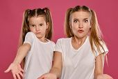 Mom And Daughter With A Funny Ponytails, Dressed In White T-shirts Are Posing Against A Pink Studio  poster