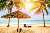 Sun Loungers Under Umbrella On The Sandy Beach With Palms By The Sea And Sky. Vacation Background. I poster