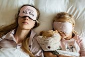 High View Of Caucasian Mother And Daughter, Stuffed Teddy Bear Toy Sleeping In Blindfolds On The Bed poster