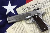 stock photo of defender  - Handgun lying over a copy of the United States constitution and the American flag - JPG