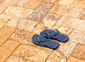 Discarded Flipflops On Paved Deck By Pool