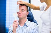 Optometry concept - handsome young man having his eyes examined by an eye doctor (color toned image;
