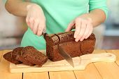 Woman slicing black bread on chopping board on wooden table close up