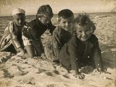 SOPOT, POLAND - CIRCA 1949: vintage photo of group of unidentified children playing on beach, circa
