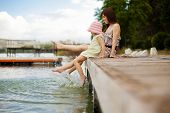 foto of pier a lake  - Young mother and her daughter splashing in the lake - JPG