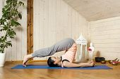 An image of a pretty woman doing yoga at home - Halasana