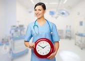Young doctor with clock at medical office