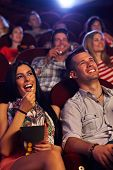 Young couple sitting in cinema, watching movie, eating popcorn, smiling.
