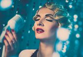 Elegant blond retro woman singer with beautiful hairdo and red lipstick
