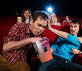 Impudent young man steal popcorn in cinema while people watching movie