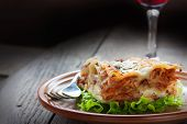 pic of wood pieces  - Italian cuisine. Freshly baked homemade lasagna with minced meat and cheese served on a piece of lettuce and red wine.