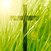 stock photo of crucifixion  - glowing christian cross on a green nature background - JPG
