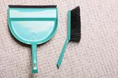 Green Sweeping Brush And Dustpan On Floor