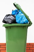 stock photo of dustbin  - A green dust bin full of rubbish sacks - JPG