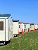 Scenic view of row of caravans in trailer park with blue sky background.