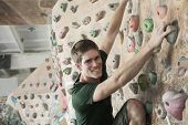 Smiling young man climbing up a climbing wall