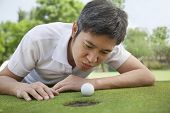 Mid adult man lying down in a golf course trying to blow the ball into the hole