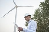 Young engineer in a hardhat looking down at a blueprint in front of a wind turbine