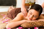 Chinese Asian woman in wellness beauty spa having aroma therapy massage with essential oil, looking