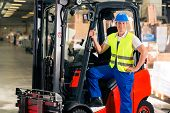 stock photo of forklift  - forklift driver in protective vest and forklift standing at warehouse of freight forwarding company - JPG