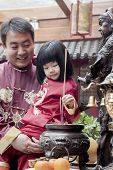 Father and daughter offering incense at the temple in Beijing