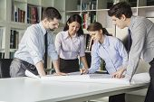 stock photo of button down shirt  - Four architects standing and planning around a table while looking down at blueprint - JPG