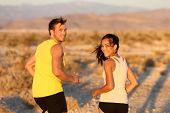 Exercise - couple running looking happy at camera. Runners jogging outside in cross-country trail run. Fit young athlete man and woman fitness runner training together in prairie nature landscape, USA
