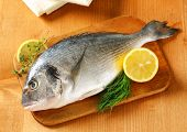 fresh sea bream with lemons and herbs, on a wooden cutting board