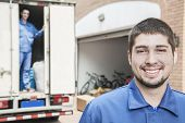 stock photo of movers  - Portrait of smiling mover with moving truck in the background - JPG