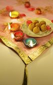 stock photo of laddu  - Indian sweets with traditional clay lamps - JPG